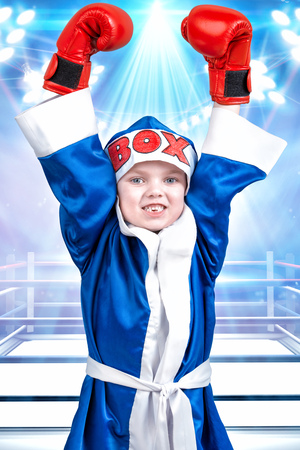 Little boy boxer with red gloves and robe in the background of the ring.Little champion.The big wins.
