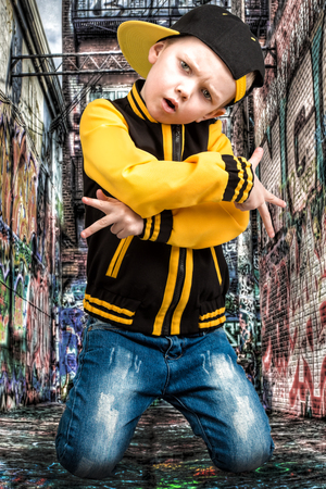 The little boy in the style of Hip-Hop. Children's fashion.Cap and jacket. The Young Rapper.Graffiti on the walls.Cool rap dj.