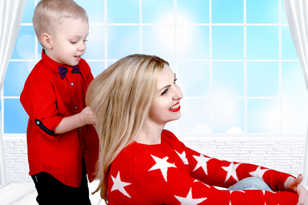 Young mother and little son playing.Child combs moms hair.The concept of a family holiday.