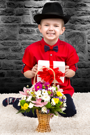 Stylish little boy in a shirt and hat with a surprise gift and a bouquet of flowers.Trendy dandy. Stock Photo