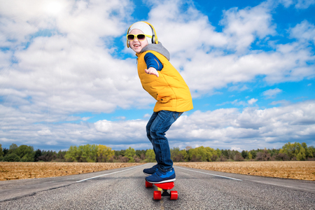 Boy doing tricks on a skateboard, skate on the road. The little boy in the style of Hip-Hop. The Young Rapper.Cool rap DJ.