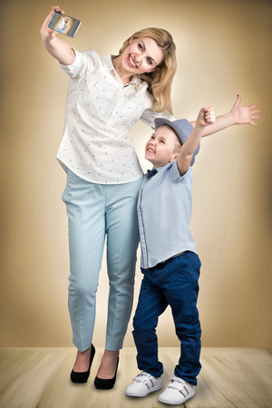 Mother and son take a selfie photo on their mobile phone.Stylish, trendy, modern Stock Photo