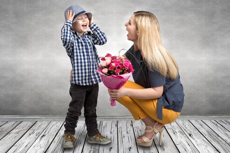 Small son gives his beloved mother a beautiful bouquet of pink roses. Spring, concept of family vacation. Womens day, mothers day.