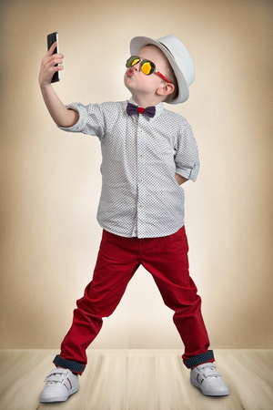 Stylish fashion boy in the hat making selfie on mobile phone, portrait.Kid's fashion.