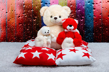 Soft Teddy bear sat on the pillow against the window.The rain drops on the window .Beautiful pillows to decorate the interior of the house. Pillow with star ornament.