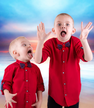 Two brothers playing and having fun, Hamming spending time together.They wear the same trendy clothing, shirts.