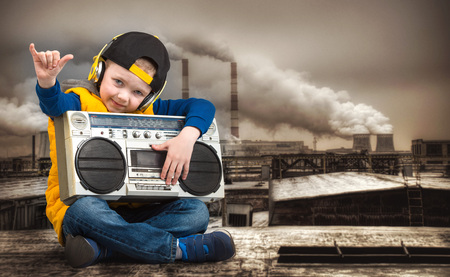 Little boy in Hip-Hop listens to the old tape recorder. The Young Rapper.Cool rap DJ.Vintage silver boom box Radio.Childrens fashion