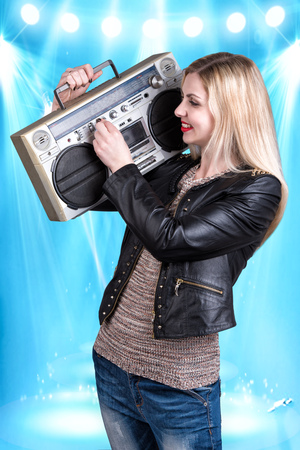 sound box: Young beautiful woman listening to music holding a retro tape recorder.