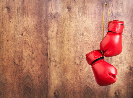 Pair of red leather boxing gloves hanging on a nail on a wooden wall.