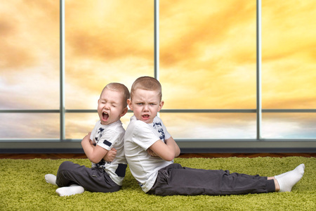 The conflict of the brother. The boys had a fight and turned in different directions. Stock Photo