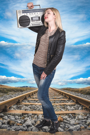 sound box: A young woman stands on the rail and listening to a vintage tape recorder.