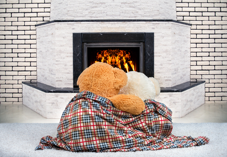 Two Teddy bear hugging and staring at the flame of the fire in the fireplace. 版權商用圖片