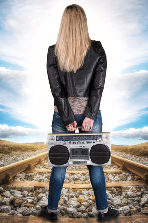 80 s: A young woman stands on the rail and holds the vintage tape recorder.