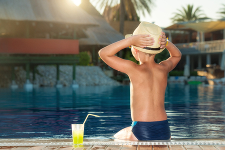 tans: A boy in a straw hat with a cocktail in a hand sitting on the pool
