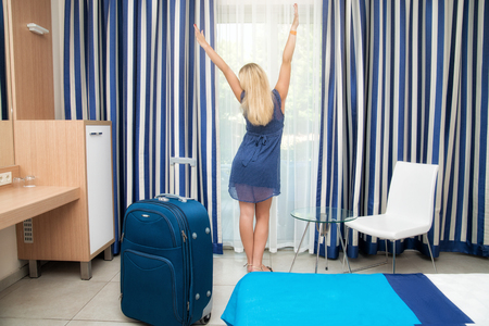 five star: Young woman with suitcase looking out the window in the hotel room.Rest after a long journey. ? Stock Photo