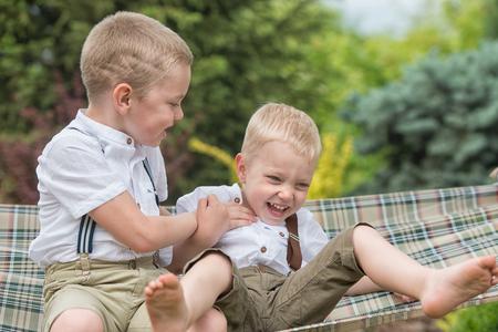 De twee broers rusten en plezier. Kinderen rijden in een hangmat.