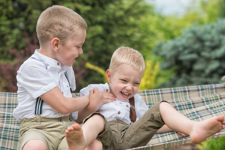 family tickle: The two brothers are resting and having fun .Children ride in a hammock.