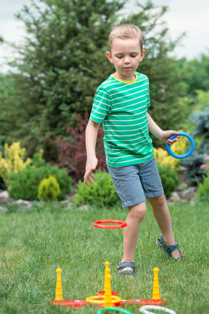 Boy playing a game of throwing rings outdoors in summer Park Standard-Bild