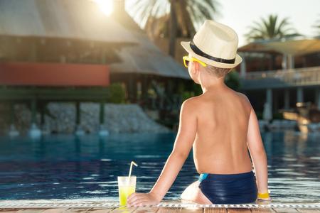 Een jongen in een strohoed met een cocktail in een hand die aan het zwembad zit