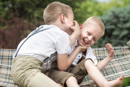 Die beiden Brüder ruhen und erzählen Geheimnisse in seinem Ohr. Jungen fahren in der Hängematte. Standard-Bild - 82036955
