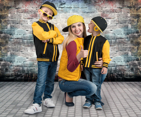 A young mother and two young sons in the style of a hip hop. Fashionable family.