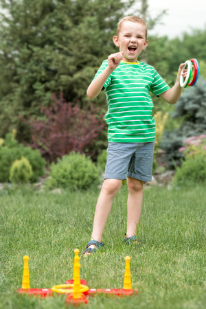 Cute boy playing a game of throwing rings outdoors in summer Park. The joy of victory. Stock Photo