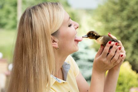 Młoda kobieta całuje małą kaczkę. Kaczka wyrywa język dziewczyny. Zdjęcie Seryjne