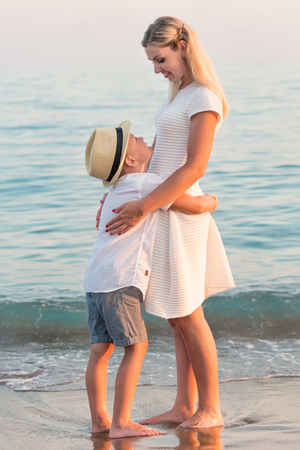 lia: Family walking on the evening beach during sunset.Mother and son embracing, looking at the sea.