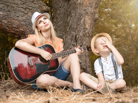 Young mother and beautiful son in the forest, sing songs under a guitar.
