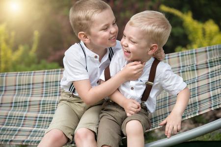 De twee broers rusten en vertellen geheimen in zijn oor. Jongens rijden in de hangmat.