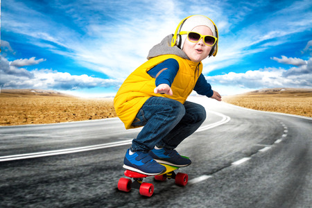 Boy doing tricks on a skateboard, skate on the road. The little boy in the style of Hip-Hop. Stock Photo