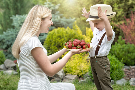 reggicalze: A young mother treats her baby son ripe fragrant strawberries.