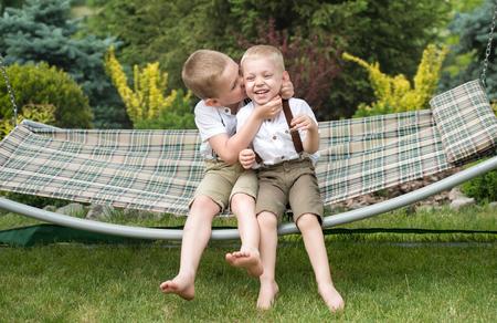 De twee broers rusten en hebben plezier. Kinderen rijden in een hangmat.