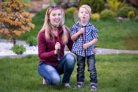 shuttlecock: Mother and little son playing badminton.