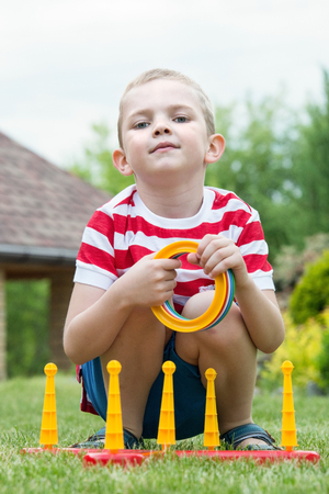 Boy playing a game of throwing rings outdoors in summer Park Stock Photo