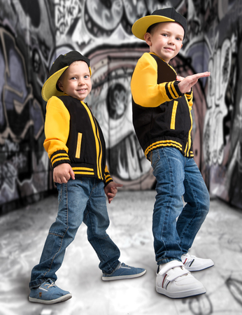 Two brothers in the style of a hip hop. Fashionable team. Graffiti on the walls. ?