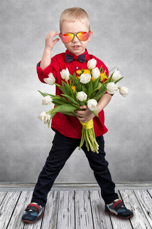 Stylish little boy holds a bouquet of spring tulips.Spring, holiday, childrens fashion. ? Stock Photo