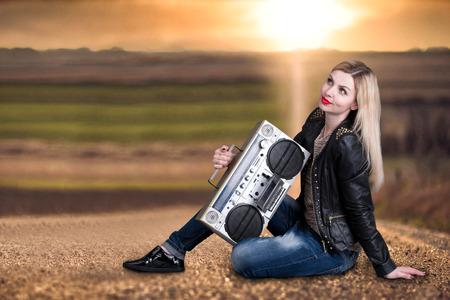grabadora: Una mujer joven se sienta en el camino y escucha una grabadora vintage. ?