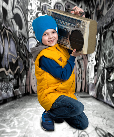 The little boy listened to a vintage tape recorder.Vintage style .Childrens fashion.Graffiti on the walls. Stock Photo