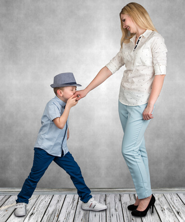 Der Junge küsst die Hand der Mutter. Standard-Bild