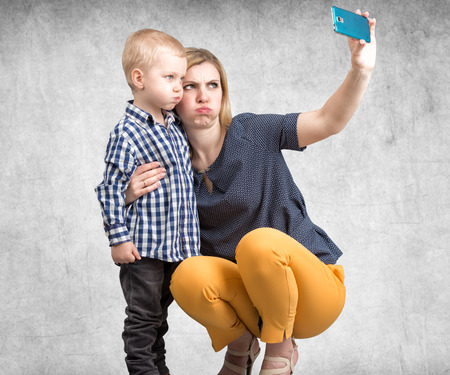 Young mother and little son are photographed on a mobile phone.