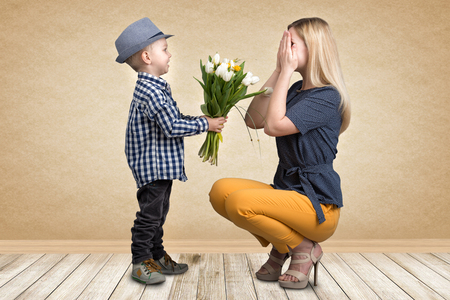 Small son gives his beloved mother a bouquet of beautiful tulips. Spring, concept of family vacation. Women's day.