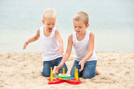 Two brothers are walking and playing on the beach. The game is a ring toss.