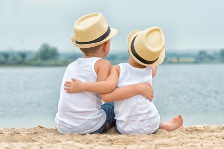 두 형제는 호수 해변에서 휴식. 어린 소년은 그의 형을 부드럽게 품는다. 스톡 콘텐츠