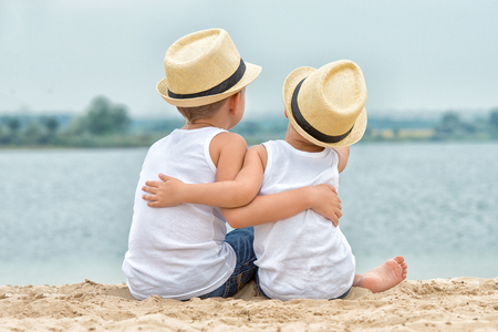 Two brothers relaxing on the beach of the lake. The little boy tenderly embraces his older brother.
