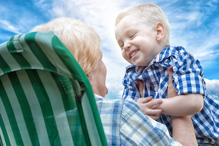 tenderly: The little boy tenderly embraces his beloved grandmother. Love generations. Stock Photo