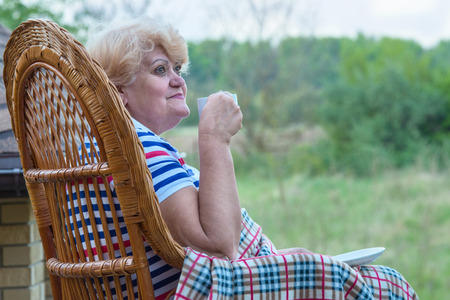 An elderly woman sits in a wicker rocking chair and drinks a Cup of coffee.Relax in a country house.