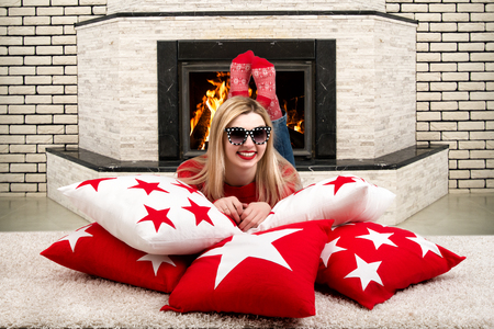 pyre: Beautiful young blonde woman lying on a pillow in the room with a fireplace and enjoying the fire in the fireplace. Pillows for home interior decorating.