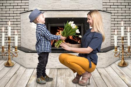 어린 아들 그의 사랑하는 어머니 아름 다운 튤립의 꽃다발을 제공합니다. 봄, 가족 휴가의 개념입니다. 여성의 날.