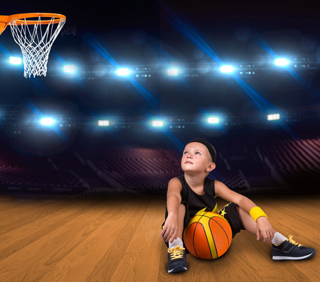 Boy basketball player with a ball sitting on the floor in the gym and dreams of great victories.
